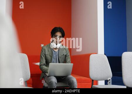 Uomo asiatico in occhiali seduti su una sedia e la digitazione sul computer portatile egli lavora online Foto Stock