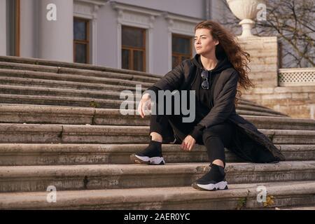 La cova elegante ragazza con i capelli neri in una giacca di