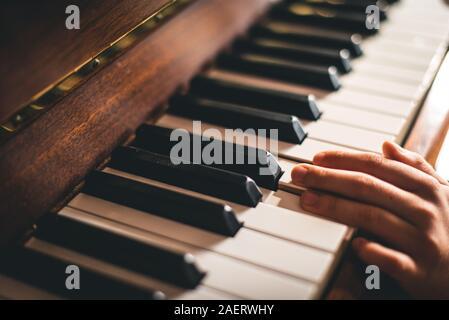 In prossimità delle dita di un bambino la mano appoggiata su tasti di pianoforte. Foto Stock