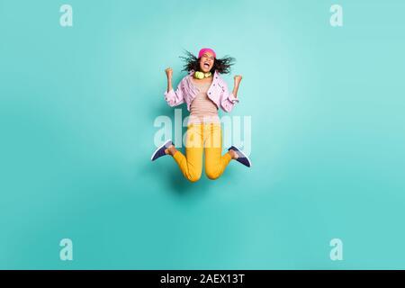Per tutta la lunghezza del corpo lato di dimensione della foto del profilo di casual positiva esecuzione di salto School girl che aspirano a venire al complesso educativo sul tempo in giallo Foto Stock