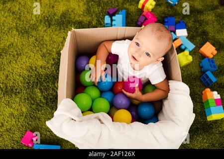 Vista superiore del bambino carino in una scatola di cartone a giocare con le palle colorate