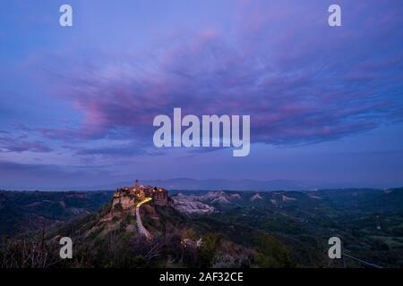 Civita di Bagnoregio, un antico insediamento etrusco, situato sulla sommità di un tufo vulcanico altopiano, illuminata di notte dopo il tramonto