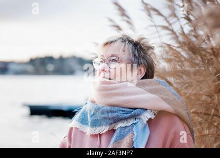 Ritratto di donna nella sua 60's cercando felice seduti fuori in autunno.