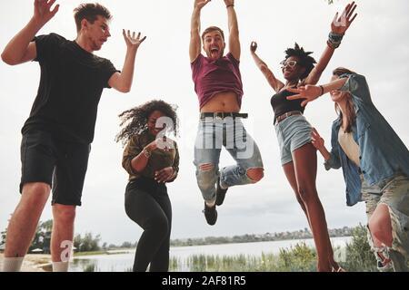 Celebrare durante il salto. Un gruppo di persone che hanno picnic sulla spiaggia. Gli amici hanno divertimento al tempo di fine settimana