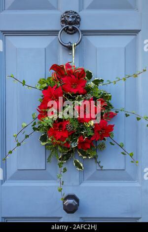 Tradizionale stagione festiva ghirlanda di Natale disposizione con fiori di colore rosso e verde fogliame appeso in grigio di una porta anteriore in corrispondenza di una casa nel Surrey, Inghilterra