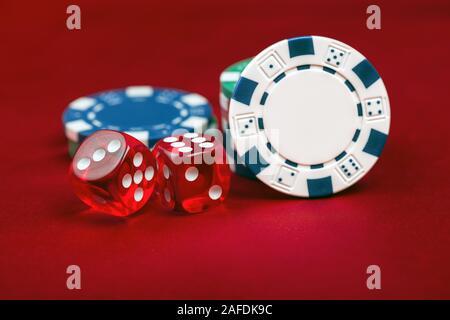 Dadi e casino chips su sfondo rosso. Il concetto di gioco d'azzardo Foto Stock