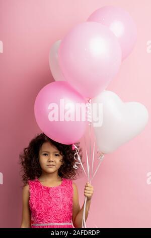 Studio verticale colpo di confuso bambina con capelli ricci, indossando abiti incantevole, tenendo bianco e rosa palloncini aria, guardando la fotocamera con embarr Foto Stock