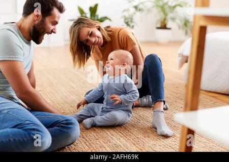 I genitori seduti sul pavimento a casa a giocare con il bambino figlio