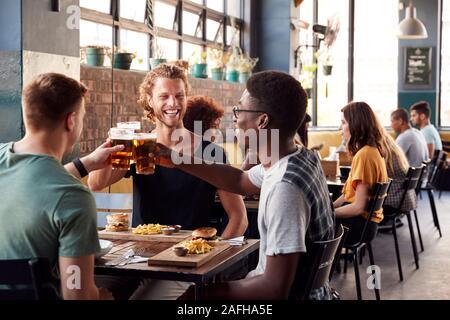 Tre giovani amici maschi incontro per un drink e il cibo facendo un toast in Ristorante Foto Stock