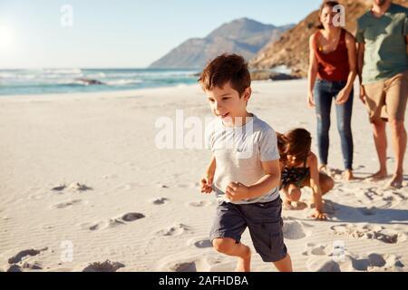 Felice bianco giovane famiglia in vacanza ad esplorare una spiaggia insieme a piena lunghezza e chiudere fino