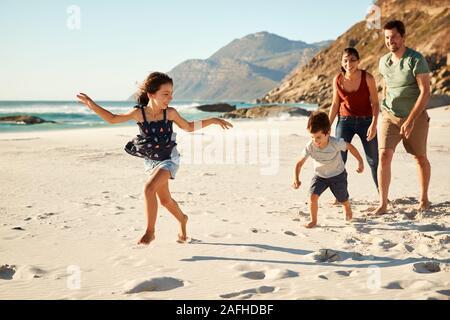 Felice bianco giovane famiglia in vacanza ad esplorare una spiaggia insieme a piena lunghezza Foto Stock