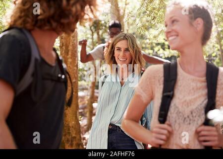 Giovani amici adulti parlando come loro escursione attraverso una foresta insieme, close up