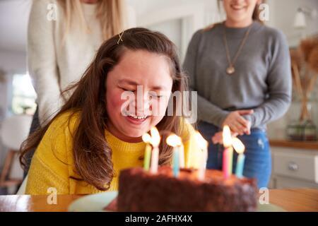 Downs la giovane donna di sindrome festeggia il compleanno a casa con torta Foto Stock