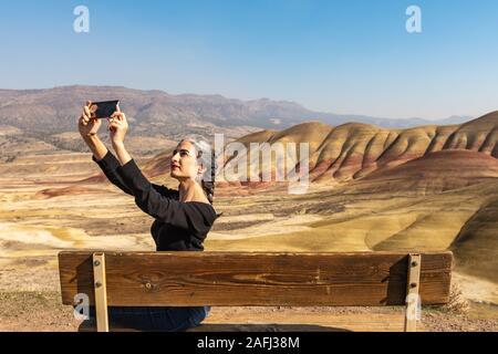 Un giovane brunette con filamenti di grigio rende selfies seduta su una panchina nel dipinto di colline si affacciano