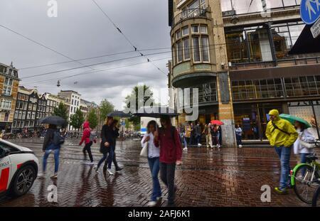Amsterdam, Olanda, Agosto 2019. Giorno di pioggia nella città vecchia. Le sagome di persone e cose si riflettono sulla strada bagnata. Persone croce La croce