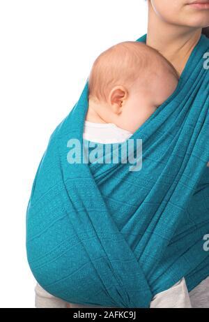 Giovane madre che porta il suo piccolo bambino in blu sling isolati su sfondo bianco. Bambino dorme in comfort, sensazione di sicurezza e protezione Foto Stock