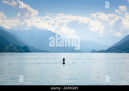 Silhouette di un uomo in piedi su un paddleboard sul Lago di Brienz in Svizzera. Colline in background. Uno stile di vita attivo, attività sportive. Sfondo pacifica, concetto motivazionale. Foto Stock