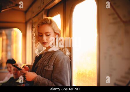 Giovane donna utilizzando smart phone durante il viaggio in treno della metropolitana