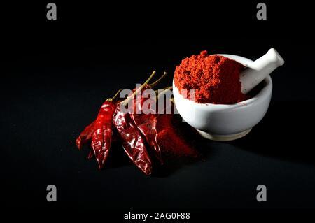 Peperoncino rosso in polvere in pestello con mortaio e peperoncino rosso su sfondo nero