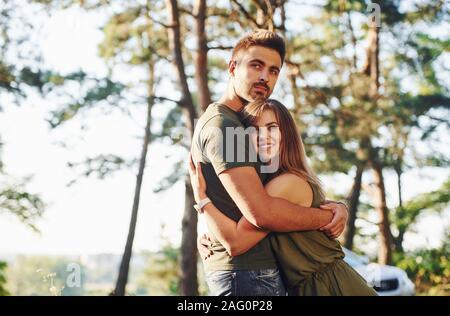 Felice insieme. Abbracciando ogni altro. Bella coppia Giovane di avere un buon tempo nella foresta di giorno Foto Stock