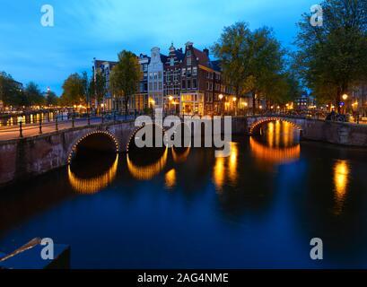 Scenario del canale Keizersgracht ad Amsterdam con il riflesso di luci vicino a un enorme edificio