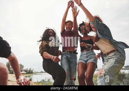 La gioventù è la danza. Un gruppo di persone che hanno picnic sulla spiaggia. Gli amici hanno divertimento al tempo di fine settimana