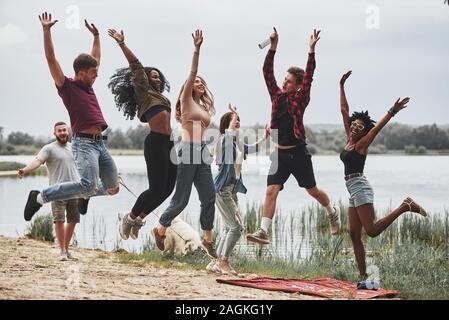 Foto nell'aria. Ognuno è il salto. Un gruppo di persone che hanno picnic sulla spiaggia. Gli amici hanno divertimento al tempo di fine settimana Foto Stock