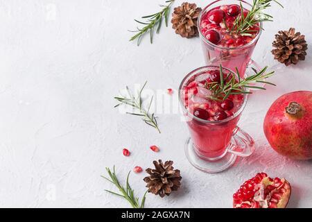 Due bicchiere di melagrana vacanze di Natale cocktail con rosmarino, mirtillo rosso, vino spumante sul tavolo bianco. Xmas drink. Spazio per il testo.