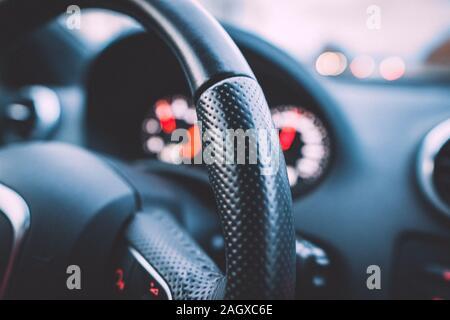 Immagine ravvicinata di un volante di sterzo e tachimetro in un'auto. Cruscotto di automobile. Dettagli del cruscotto con luci di indicazione.Auto quadro della strumentazione. Cruscotto Foto Stock