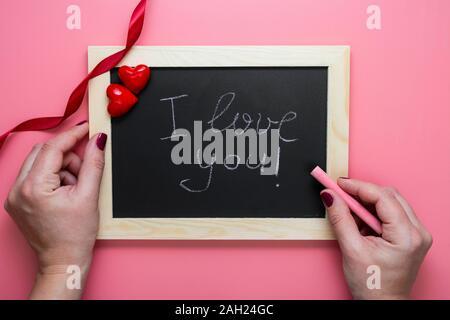 Il giorno di San Valentino sfondo. Mani femminili writting ti amo messaggio sul telaio di lavagna, cuori e nastro rosso, piatto lay mock up con spazio di copia