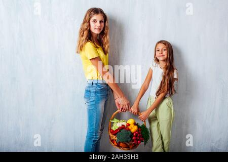I bambini seduti con verdure fresche mangiare sano frutta Foto Stock