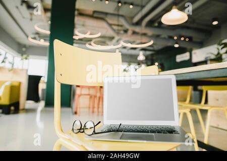 Business, notebook e i bicchieri sulla sedia in ufficio coworking Foto Stock