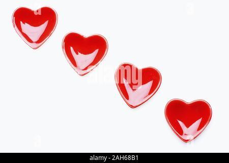 Ceramica cuori lucido in colore rosso acceso collocato in linea diagonale e isolato su sfondo bianco, vista dall'alto e copia di spazio. Il giorno di San Valentino la cena decorazione Foto Stock