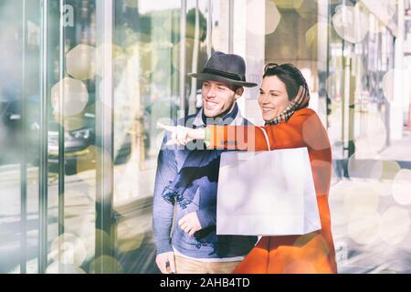 Giovane uomo e donna vestito in abiti invernali vetrine, durante la stagione delle vacanze - Puntamento e felice con un sorriso - in città durante il giorno wit