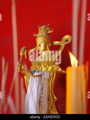 Statua dorata di una dea buddista contro la parete rossa. Le candele e i bastoncini di incenso in primo piano. Foto Stock