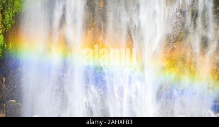 Vista ravvicinata della Tumpak Sewu cascate noto anche come Coban Sewu con un bellissimo arcobaleno formata dalla rifrazione della luce in goccioline d'acqua.