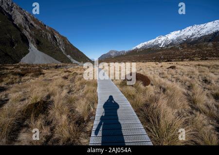Il Boardwalk percorso con ombra di fotografo con fotocamera, Hooker Valley a piedi, dal Parco Nazionale Aoraki/Mount Cook, Alpi del sud, Canterbury, Isola del Sud, Foto Stock