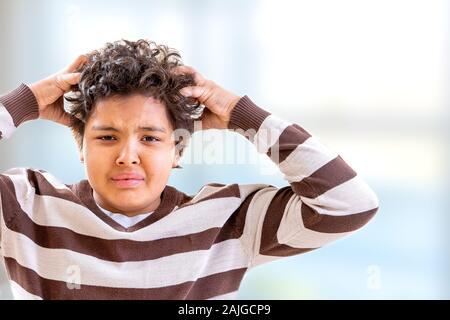 Ragazzo di stress di graffiare i suoi capelli con espressione confusa Foto Stock