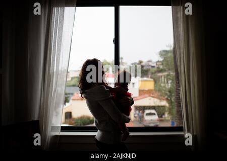 Fine anni trenta Madre tenendo bambino davanti alla finestra per Silouette