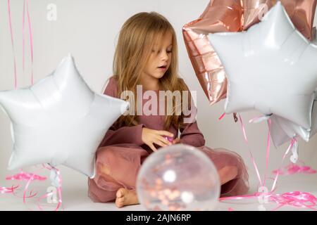 Felice brightful immagine di carino gioiosa bambina in tulle gonna seduta sul presente con palloncini su sfondo bianco Foto Stock