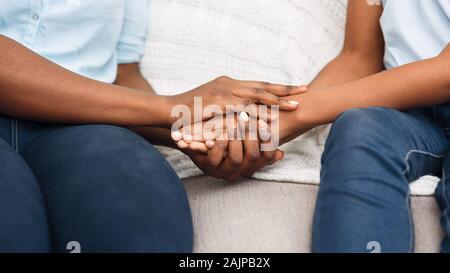 Close up Nero donna e bambino seduto sul lettino tenendo le mani dicendo Siamo spiacenti, scusarsi