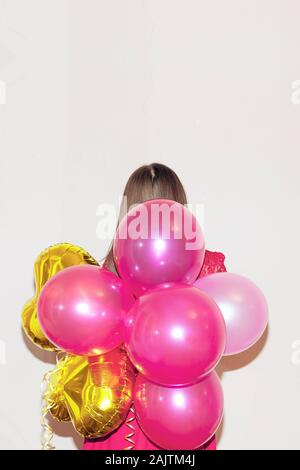 Giovane bella ragazza in abito rosso sorge sul lato posteriore tenendo un mazzetto di colorati palloncini d'aria. Il giorno di San Valentino, compleanno, la giornata della donna, anniversario Foto Stock