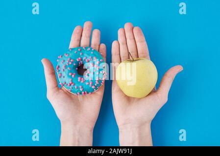 Donna scegliendo tra apple e ciambella nelle sue mani. Cibo sano concetto Foto Stock