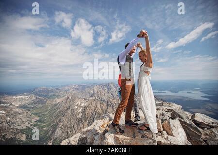 Sposa e Ginestra festeggiano dopo essersi sposati sulla cima della montagna Foto Stock