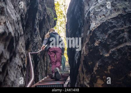 donna sale le scale attraverso una spaccatura nelle rocce Foto Stock