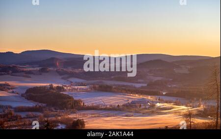 alba in montagna - inverno paesaggio collinare con boschi, alberi e prati (con brina e neve) Foto Stock