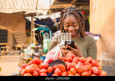 Giovane donna africana in un locale il mercato africano di visualizzazione dei contenuti sul suo telefono e guardando sorpreso Foto Stock