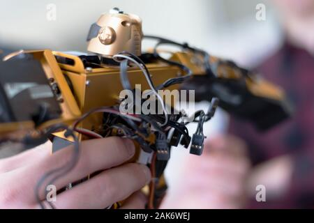 Giovane donna ingegnere di lavoro sul progetto di robotica. Scienziato ingegnere progetta piccolo robot umani, impostazioni di intelligenza artificiale robot umanoide