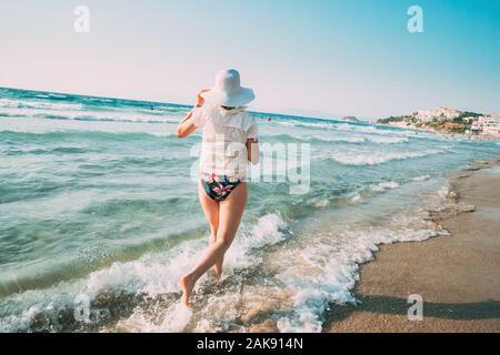 Giovane donna caucasica donna in estate Hat corre lungo la riva del mare mare spiaggia. Vacanza mare sulla spiaggia dell'oceano. Foto Stock