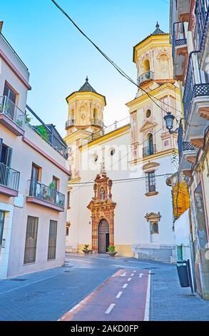 La modesta facciata di San Felipe Neri Chiesa Parrocchiale con due campanili e intagliato del telaio della porta, Malaga, Spagna Foto Stock